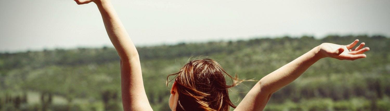 eine Frau freut sich und reist die Arme hoch